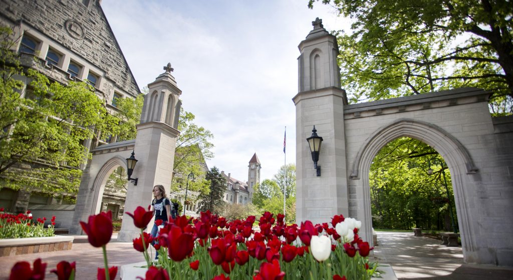 A student makes her way through the Sample Gates during a sunny, spring day on Tuesday, May 5, 2015.